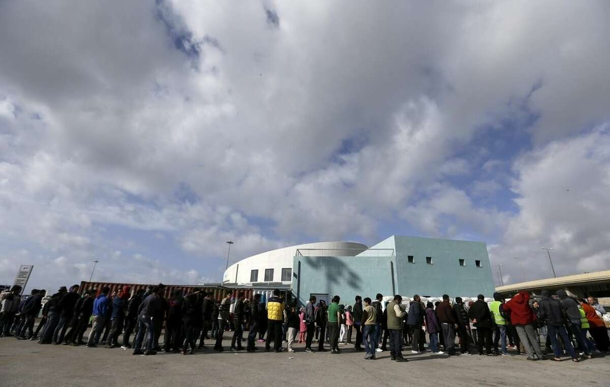 People wait in queues to receive food distributed by non-governmental organizations at the Athens' port of Piraeus where over 2,000 stranded refugees and migrants stay at the passenger terminal buildings and their tents, on Monday, March 7, 2016. European Union leaders will be looking to boost aid to Greece as the Balkan migrant route is effectively sealed, using Monday's summit as an attempt to restore unity among the 28 member nations after months of increasing bickering and go-it-alone policies. (AP Photo/Thanassis Stavrakis)