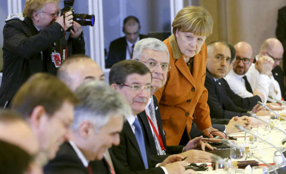 German Chancellor Angela Merkel, center, takes her seat during a lunch with other leaders at an EU summit in Brussels on Monday, March 7, 2016. European Union leaders arrived in Brussels Monday to press Turkey to do more to stop migrants entering Europe and to shore up support for Greece, where thousands of people are stranded. (Olivier Hoslet, Pool Photo via AP)