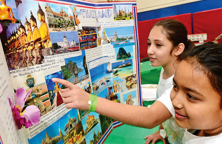 K.T. Murphy School fourth-graders Juliana Macalusa and Leila Guadalupe look over their display for Thailand during the 6th annual Multiculturism Fair.
