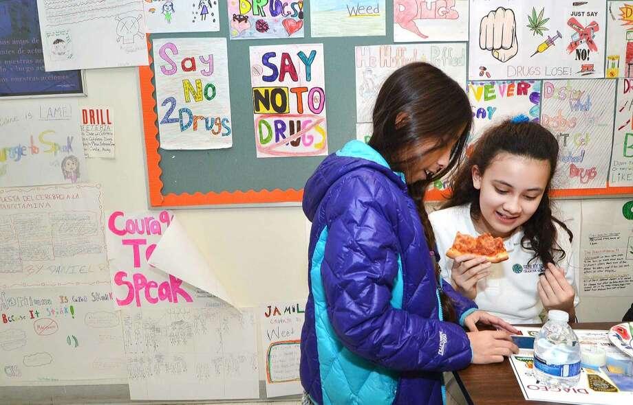 Hour Photo/Alex von Kleydorff Carolina Martinez and best friend Victoria Silva-Meza enjoy pizza during the Courage to Speak Family Night Program at West Rocks School