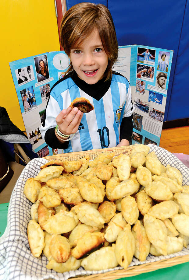 K.T.Murphy School second-grader Santiago Petraglia tries a beef epanada from Argentina during the 6th annual Multiculturism Fair at KTMurphy School in Stamford Saturday. The fair featured interactive displays and food tastings from 19 different countries.
