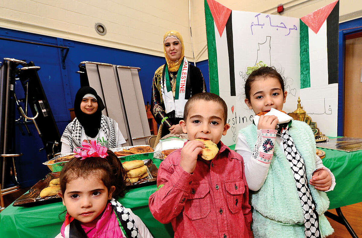 Bisan Sedda, Banan Sedda and Paylasan Sedda eat traditional Palestinian food during the 6th annual Multiculturism Fair at K.T.Murphy School in Stamford Saturday. The fair featured interactive displays and food tastings from 19 different countries.