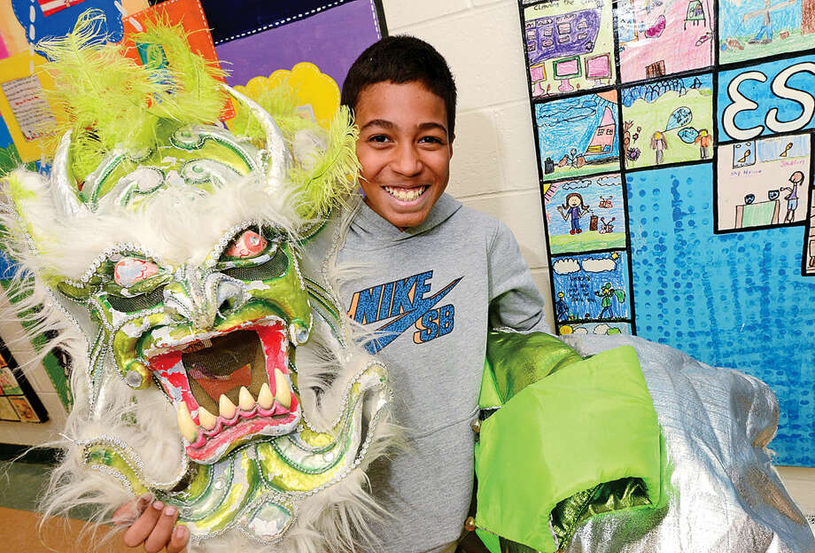 Justin Ortega displays a Carnival mask during the 6th annual Multiculturism Fair at K.T. Murphy School in Stamford Saturday. The fair featured interactive displays and food tastings from 19 different countries.