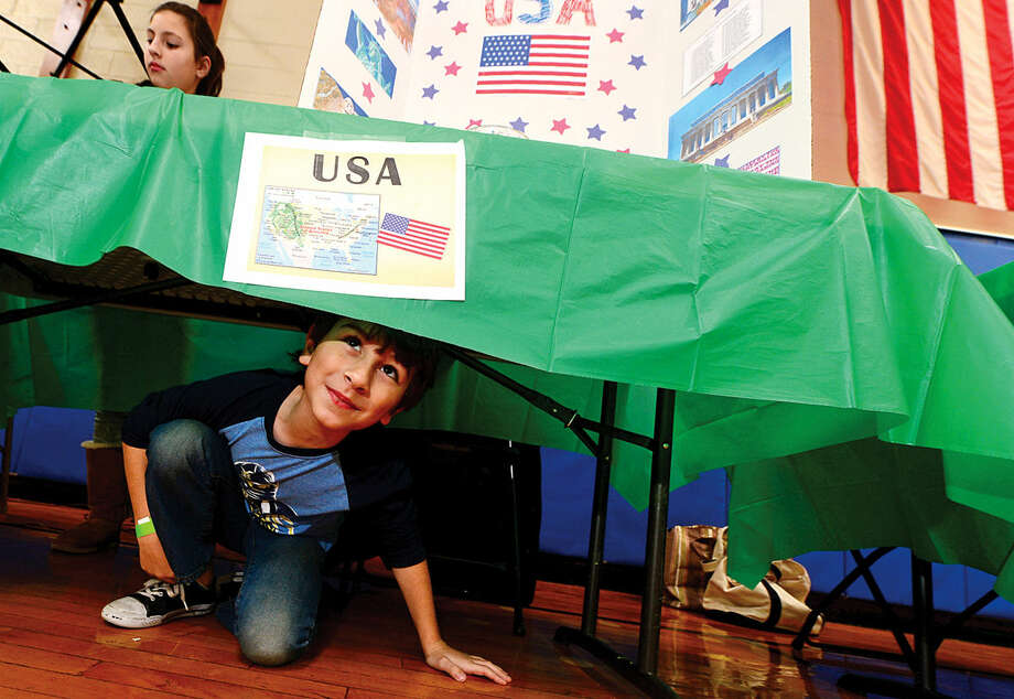 K.T. Murphy School students Athan Gzavaras and his sister Zoina Gzavaras man the table for the United States during the 6th annual Multiculturism Fair at K.T. Murphy School in Stamford Saturday. The fair featured interactive displays and food tastings from 19 different countries.