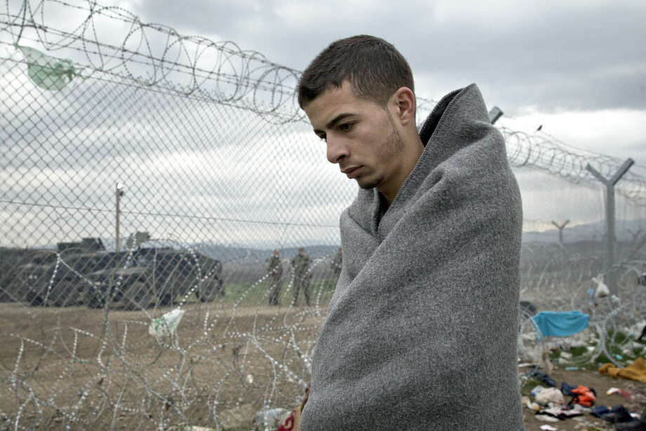 A migrant walks by the fence separating Greece and Macedonia at the northern Greek border station of Idomeni, Monday, March 7, 2016. Greek police officials say Macedonian authorities have imposed further restrictions on refugees trying to cross the border, saying only those from cities they consider to be at war can enter as up to 14,000 people are trapped in Idomeni, while another 6,000-7,000 are being housed in refugee camps around the region.(AP Photo/Vadim Ghirda)