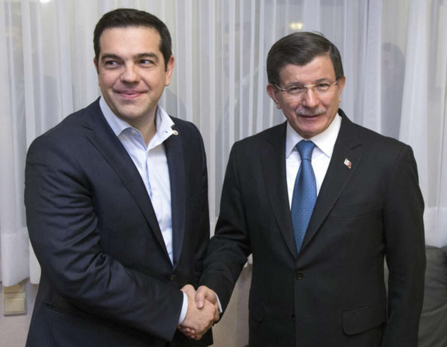 Turkish Prime Minister Ahmet Davutoglu, right, shakes hands with Greek Prime Minister Alexis Tsipras during a meeting on the sidelines of an EU summit in Brussels on Monday, March 7, 2016. European Union leaders are holding a summit in Brussels on Monday with Turkey to discuss the current migration crisis. (Yves Herman, Pool Photo via AP)