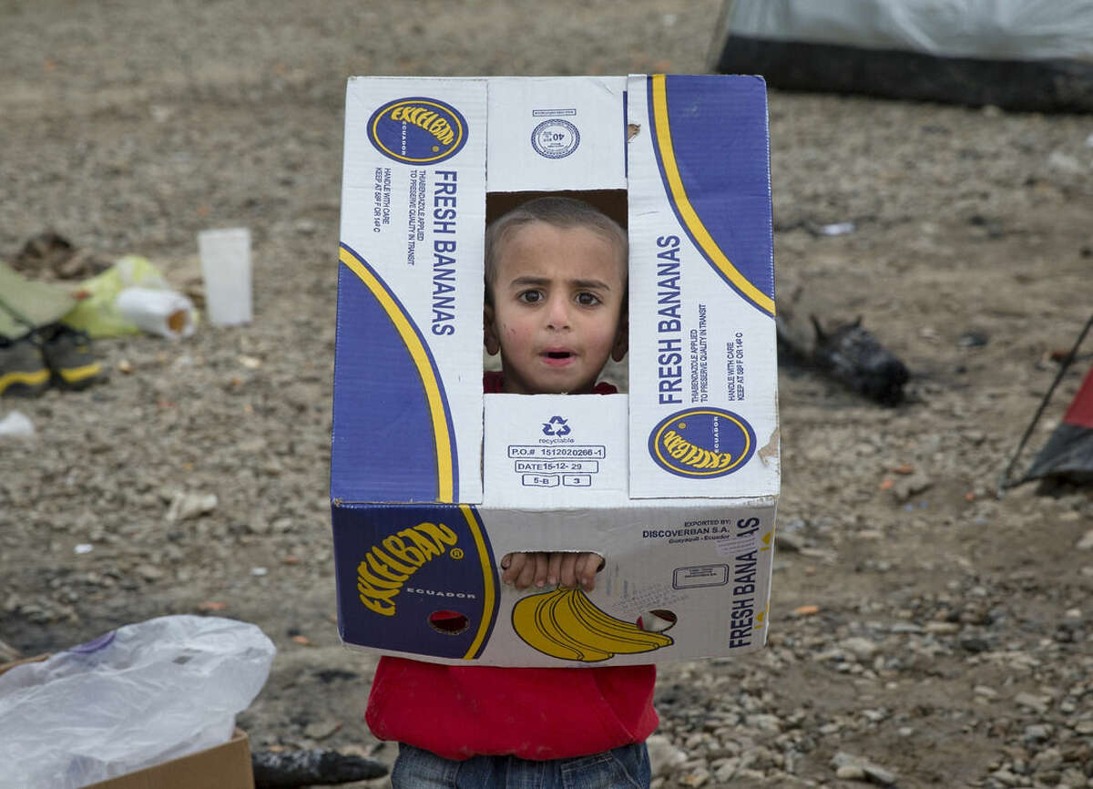 A child plays with a cardboard box at the northern Greek border station of Idomeni, Sunday, March 6, 2016. Greek police officials say Macedonian authorities have imposed further restrictions on refugees trying to cross the border, saying only those from cities they consider to be at war can enter as up to 14,000 people are trapped in Idomeni, while another 6,000-7,000 are being housed in refugee camps around the region.(AP Photo/Vadim Ghirda)