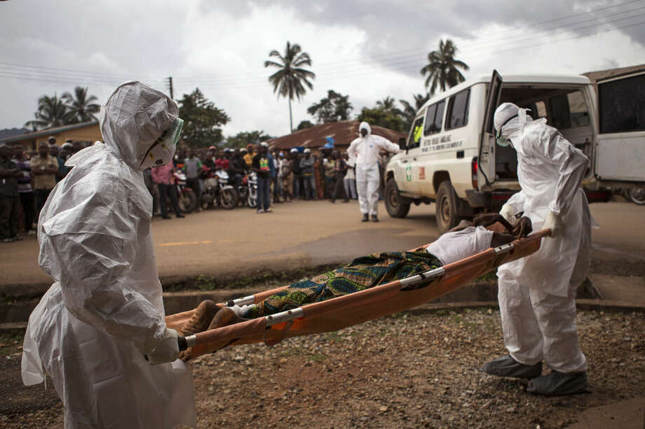 FILE - In this Wednesday, Sept. 24, 2014 file photo, healthcare workers load a man suspected of suffering from the Ebola virus onto an ambulance in Kenema, Sierra Leone. Sierra Leone imposed a quarantine in a fishing district of the capital city, Freetown, after at least five new Ebola cases were confirmed there, an official said Saturday, Feb. 14, 2015. (AP Photo/ Tanya Bindra, File)