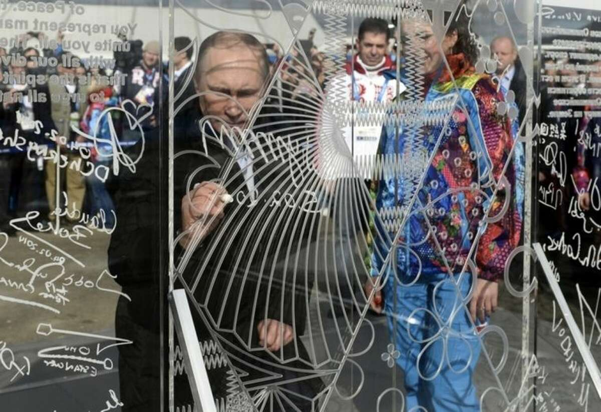 Russian President Vladimir Putin signs a wall while visiting the Coastal Cluster Olympic Village ahead of the Sochi 2014 Winter Olympics on Wednesday, Feb. 5, 2014, in Sochi, Russia. (AP Photo/RIA-Novosti, Alexei Nikolsky, Presidential Press Service)