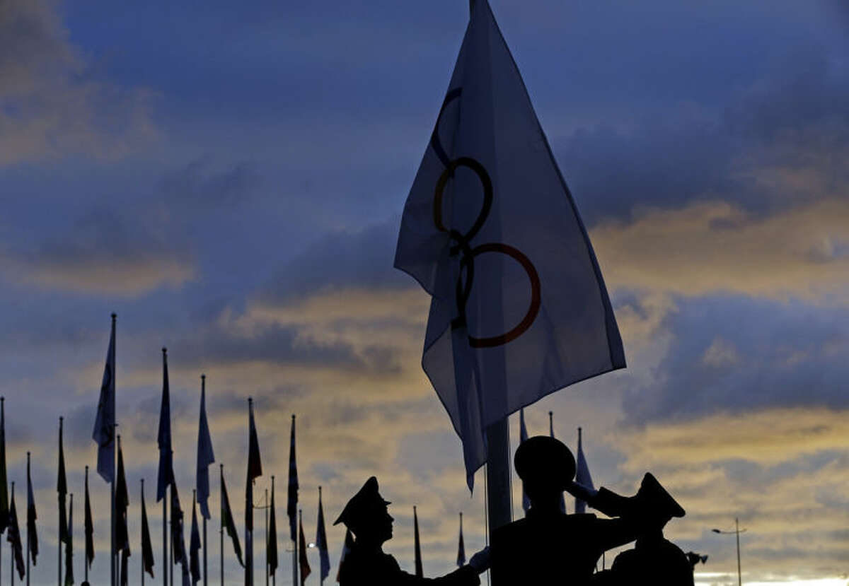 Members of a Russian honor guard raise an Olympic flag during a welcoming ceremony at the 2014 Winter Olympics, Thursday, Feb. 6, 2014, in Sochi, Russia. (AP Photo/Morry Gash)