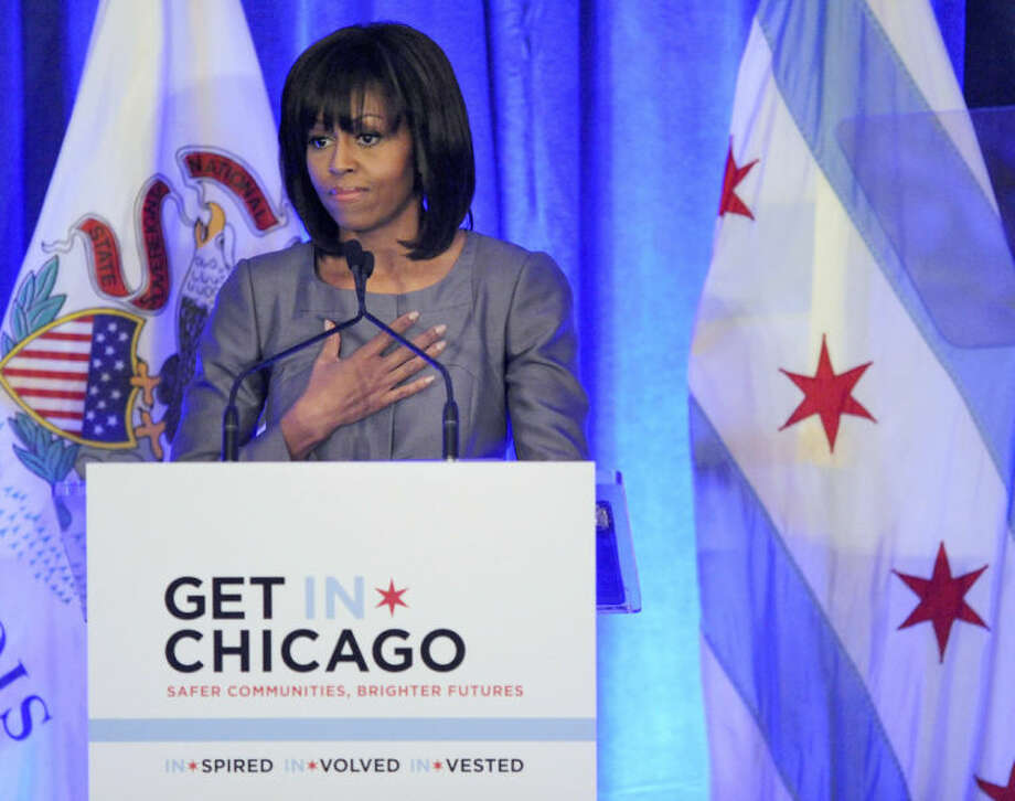 FILE - In this April 10, 2013 file photo, first lady Michelle Obama speaks at a luncheon in Chicago about the death of 15-year-old Hadiya Pendleton who was shot and killed Jan. 29, 2013 in a park during a gang dispute she had nothing to do with about a mile from the first family's Chicago home. The low point so far in Chicago's closely watched battle with street gangs may have been the day Feb. 9, 2013, when the first lady came home for Hadiya's funeral. Since Pendleton's death, the number of homicides and other violent crimes that turned Chicago into a national symbol of gun violence have fallen sharply after the city and police changed strategies. (AP Photo/Paul Beaty, File)