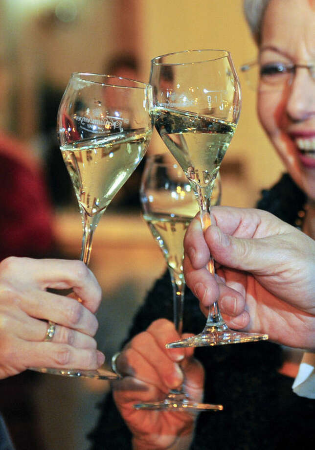 In this picture taken Saturday, Feb. 1, 2014 guests of the Ball de Pharmacy toast with their glasses of sparkling wine at the Hofburg palace in Vienna, Austria. Just when it seemed that Austria survived the Eurocrisis unscathed, austerity has hit _ in the form of a tax on sekt, the country's version of champagne. At less than one euro a bottle, the planned levy pales in severity compared to the hardships imposed on citizens of other EU nations worst hit by the past five years of economic meltdown, It is also only one of several tax hikes that will see Austrians also paying more for luxury cars and tobacco products as of next month _ yet it seems to be causing the most furor. (AP Photo/Hans Punz)