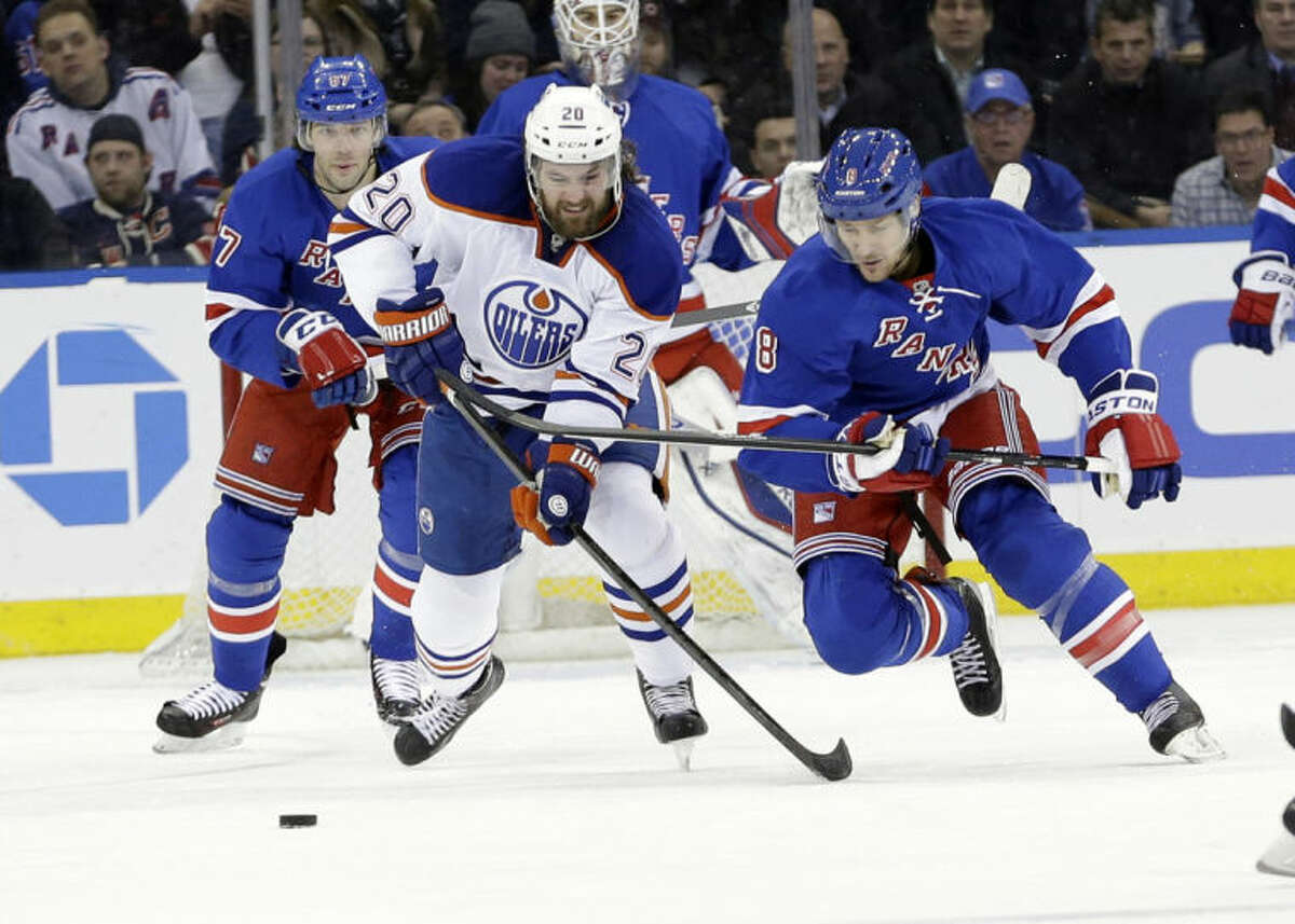 Edmonton Oilers' Luke Gazdic (20) and New York Rangers' Kevin Klein (8) fight for control of the puck during the second period of an NHL hockey game on Thursday, Feb. 6, 2014, in New York. (AP Photo/Frank Franklin II)