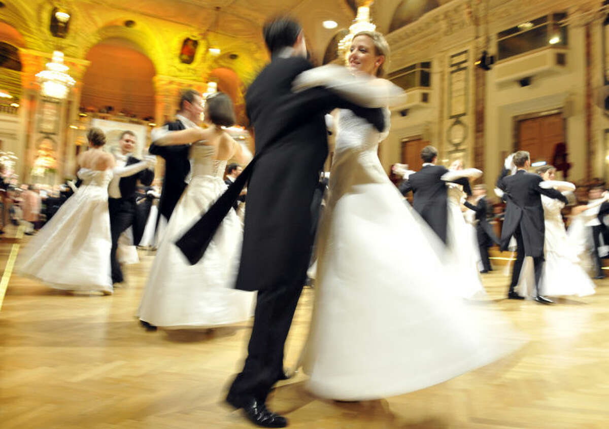 In this photo taken Saturday, Feb. 1, 2014 members of the opening committee perform during the opening of the Ball de Pharmacy at the Hofburg palace in Vienna, Austria. Just when it seemed that Austria survived the Eurocrisis unscathed, austerity has hit _ in the form of a tax on sekt, the country?'s version of champagne. At less than one euro a bottle, the planned levy pales in severity compared to the hardships imposed on citizens of other EU nations worst hit by the past five years of economic meltdown, It is also only one of several tax hikes that will see Austrians also paying more for luxury cars and tobacco products as of next month _ yet it seems to be causing the most furor. (AP Photo/Hans Punz)