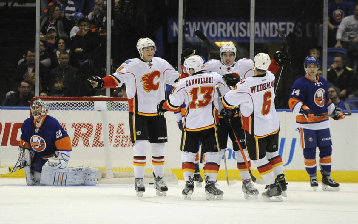 Calgary Flames' Joe Colborne (8), Mike Cammalleri (13) and Dennis Wideman (6) congratulate Sean Monahan (23) after he scored a goal against New York Islanders goalie Evgeni Nabokov (20) as Islanders' Thomas Hickey (14) looks on in the second period of an NHL hockey game, Thursday, Feb. 6, 2014, in Uniondale, N.Y. (AP Photo/Kathy Kmonicek)