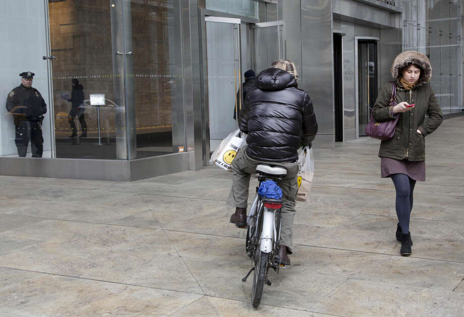 """In this March 4, 2016 photo, a bicyclist rides on a sidewalk in New York. The city that pioneered """"broken windows policing"""" is retooling its longtime strategy of cracking down hard on people who commit minor offenses, like public drinking, littering, riding a bicycle on the sidewalk or marijuana possession. (AP Photo/Mark Lennihan)"""