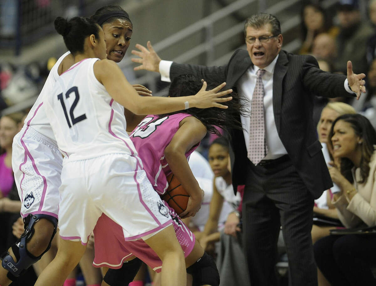 Connecticut's Morgan Tuck, back left, and Saniya Chong guard Tulane's Courtnie Latham, center, as Connecticut head coach Geno Auriemma, right, looks on during the first half of an NCAA college basketball game, Saturday, Feb. 14, 2015, in Storrs, Conn. (AP Photo/Jessica Hill)