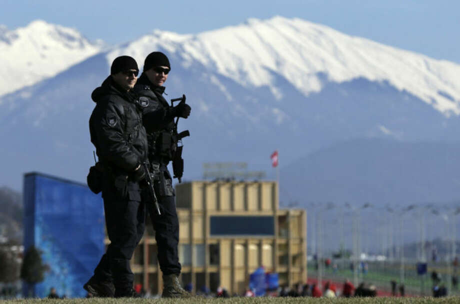"Heavily-armed Russian military flash a ""thumbs up"" while patrolling Olympic Park prior to opening ceremony at the 2014 Winter Olympics, Friday, Feb. 7, 2014, in Sochi, Russia. (AP Photo/Robert F. Bukaty)"
