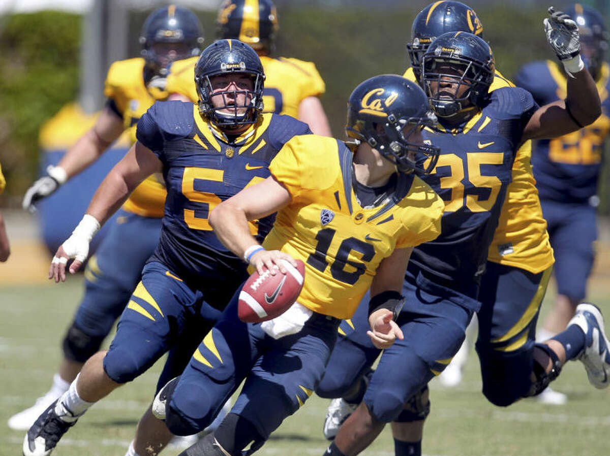 In this April 21, 2012 photo, quarterback Allan Bridgford (16) of California's Gold team is pressured by Austin Clark (54) and Ted Agu (35) of California's Blue team in the first half of their California Football Spring Experience game at Edwards Stadium in Berkeley, Calif. Agu died Friday morning, Feb. 7, 2014. He was 21. The school announced Agu's death and said its thoughts and prayers were with Agu's family, friends and teammates. The school said it would give more information about the circumstances later. (AP Photo/Bay Area New Group, Ray Chavez) MAGS OUT/LOCALS MUST CREDIT