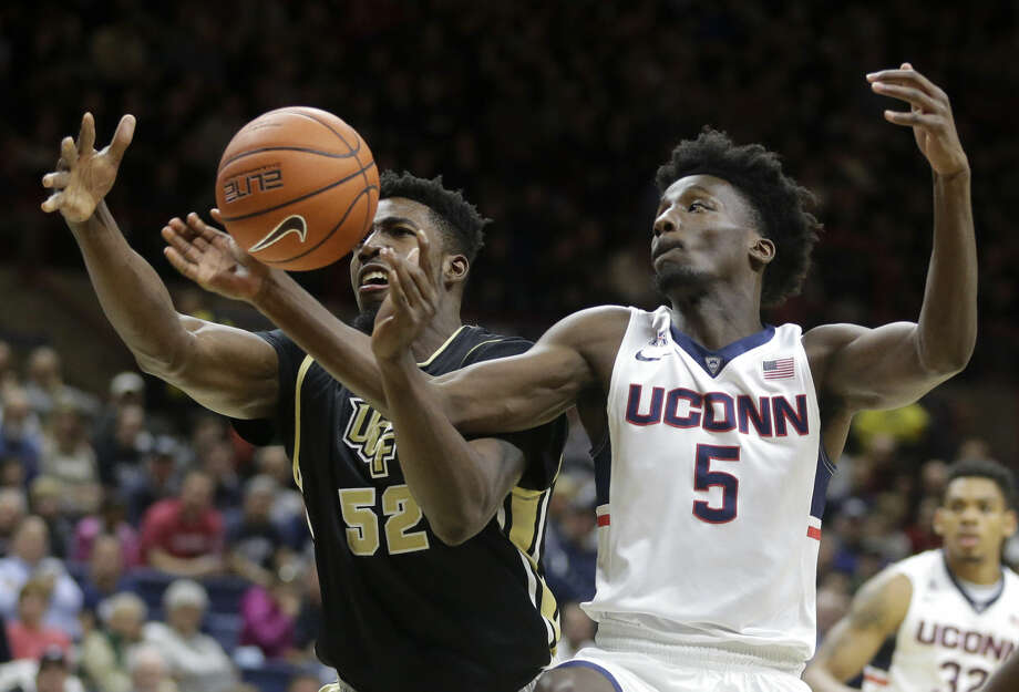Central Florida's Staphon Blair (52) vies for control of the ball with Connecticut's Daniel Hamilton (5) in the first half of an NCAA college basketball game Sunday, March 6, 2016, in Storrs, Conn. (AP Photo/Steven Senne)