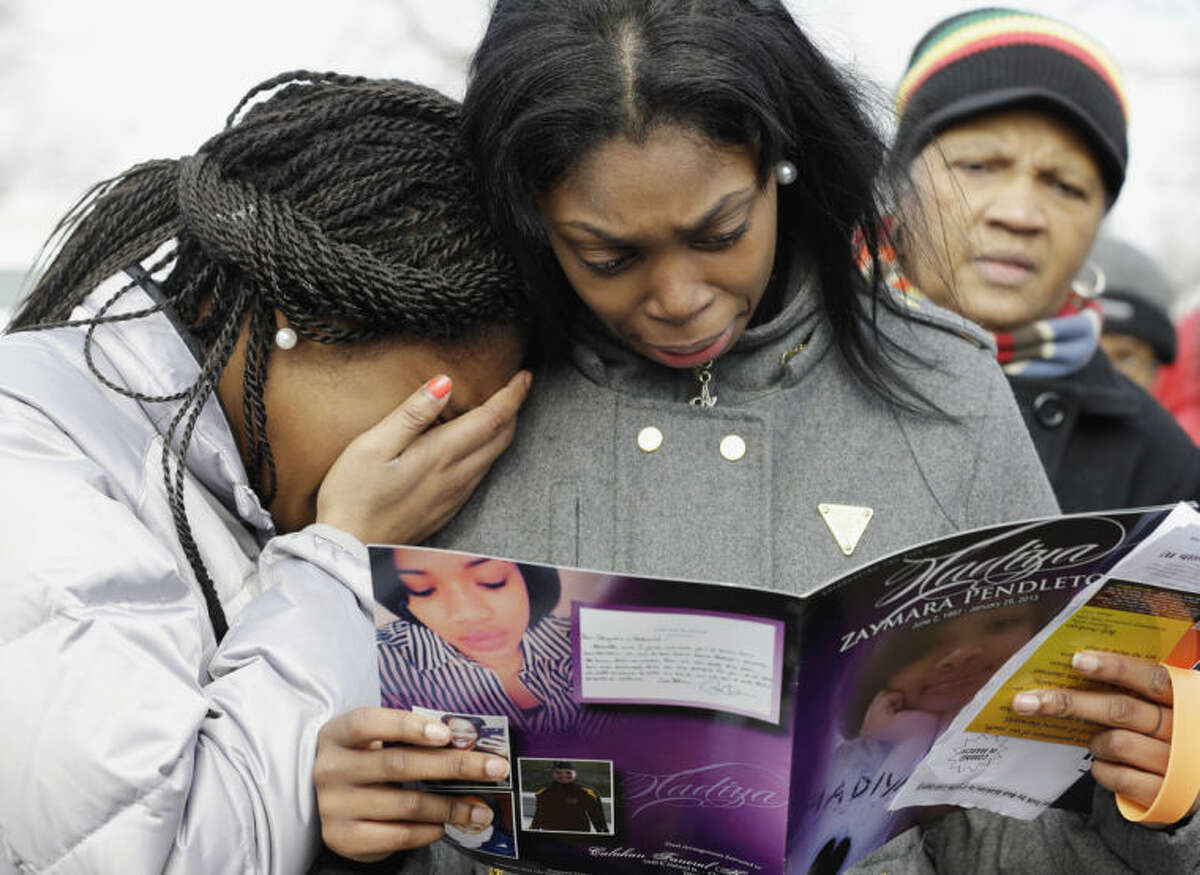 FILE - In this Feb. 9, 2013 file photo, Danyia Bell, 16, left, and Artureana Terrell, 16, react as they read a program after the funeral service for 15-year-old Hadiya Pendleton outside the Greater Harvest Missionary Baptist Church in Chicago. Hundreds of mourners and dignitaries including first lady Michelle Obama packed the funeral service for the Chicago teen whose killing catapulted her into the nation's debate over gun violence. Since her death, the number of homicides and other violent crimes that turned Chicago into a national symbol of gun violence have fallen sharply after the city and police changed strategies. (AP Photo/Nam Y. Huh, File)
