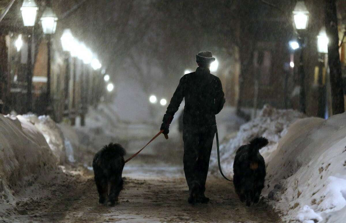 A man walks two dogs as snow falls on Beacon Hill in Boston, Saturday, Feb. 14, 2015. A blizzard warning was in effect for coastal areas from Connecticut to Maine on Saturday for a fourth major storm in less than a month, promising heavy snow and powerful winds to heap more misery on a region that has already seen more than 6 feet of snow in some areas. (AP Photo/Michael Dwyer)(AP Photo/Michael Dwyer)