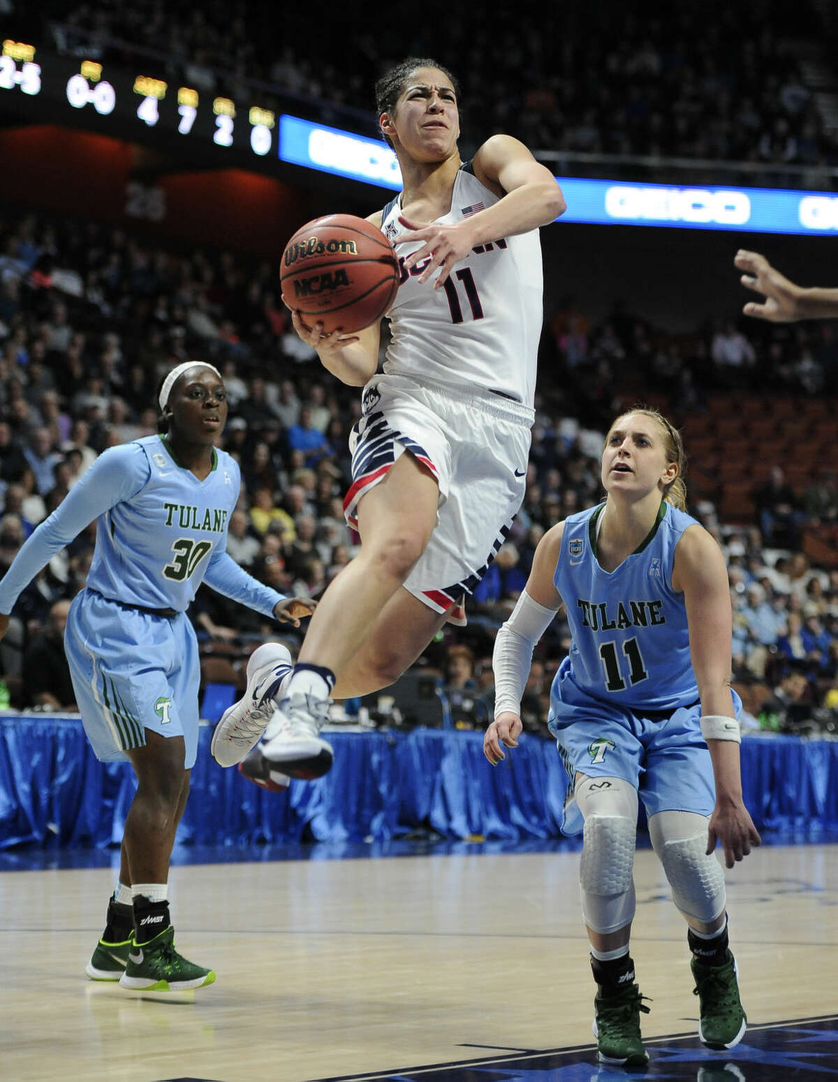 Connecticut's Kia Nurse, center, drives to the basket as Tulane's Tierra Jones, left, and Tulane's Leslie Vorpahl, right, defend, during the first half of an NCAA college basketball game in the American Athletic Conference tournament semifinals at Mohegan Sun Arena, Sunday, March 6, 2016, in Uncasville, Conn. (AP Photo/Jessica Hill)