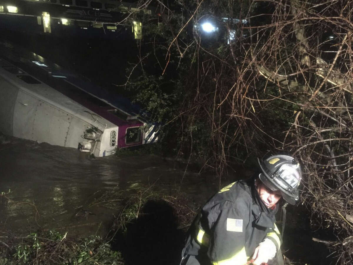 In this image provided the Alameda County Fire Department, first responders work the scene after a car of a commuter train plunged into Alameda Creek after the train derailed Monday, March 7, 2016, in Alameda County, Calif., about 45 miles east of San Francisco. Crews had to fight the creek's fast-moving currents to pull riders from the partially submerged rail car, Alameda County Sheriff's Sgt. Ray Kelly said. (Aisha Knowles/Alameda County Fire Department via AP) MANDATORY CREDIT
