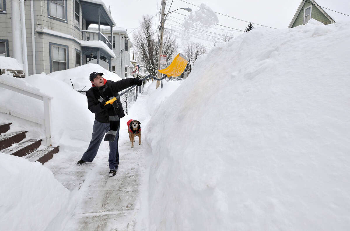 Lee Anderson adds to the pile of snow beside the sidewalk in front of his house in Somerville, Mass., Tuesday, Feb. 10, 2015, as his dog Ace looks on. The latest snowstorm left the Boston area with another two feet of snow and forced the MBTA to suspend all rail service for the day. (AP Photo/Josh Reynolds)