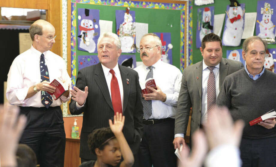Hour Photo/Alex von Kleydorff Norwalk Rotary Club members Edward Paul, Harry Rilling, Tom Vetter, Brian Falkowski and Glenn Ianaccone pass out dictionaries to third graders at Cranbury School