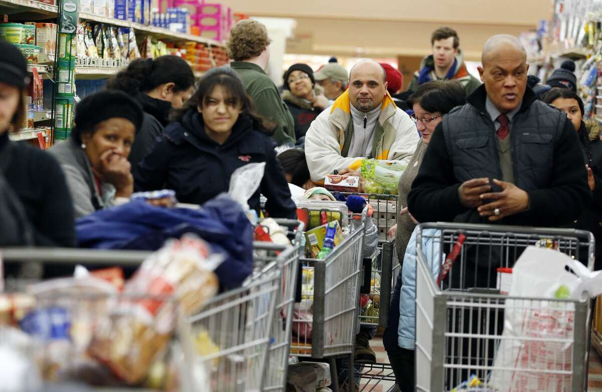 Enzo Pocaro, center, of Boston, waits in a long checkout line at the Market Basket in Chelsea, Mass., Saturday, Feb. 14, 2015. A blizzard warning was in effect for coastal areas from Connecticut to Maine on Saturday for a fourth major storm in less than a month, promising heavy snow and powerful winds to heap more misery on a region that has already seen more than 6 feet of snow in some areas. (AP Photo/Michael Dwyer)