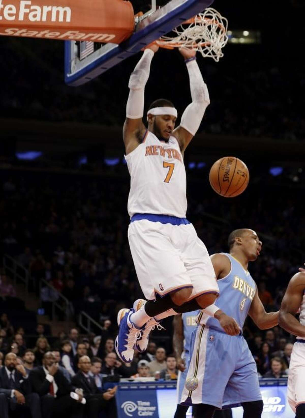 New York Knicks' Carmelo Anthony (7) dunks next to Denver Nuggets' Randy Foye (4) during the first half of an NBA basketball game Friday, Feb. 7, 2014, in New York. (AP Photo/Frank Franklin II)