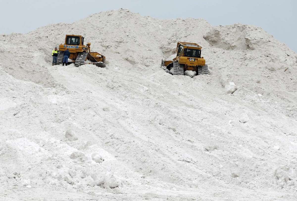 A pair of bulldozers sit on a giant snow pile at a