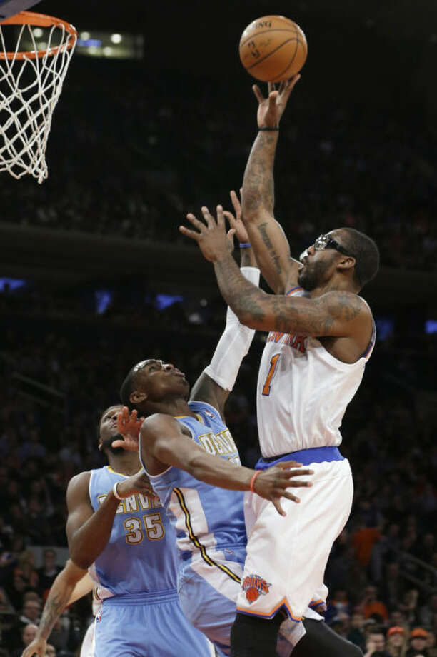 New York Knicks' Amare Stoudemire (1) shoots over Denver Nuggets' Quincy Miller (30) during the first half of an NBA basketball game Friday, Feb. 7, 2014, in New York. (AP Photo/Frank Franklin II)