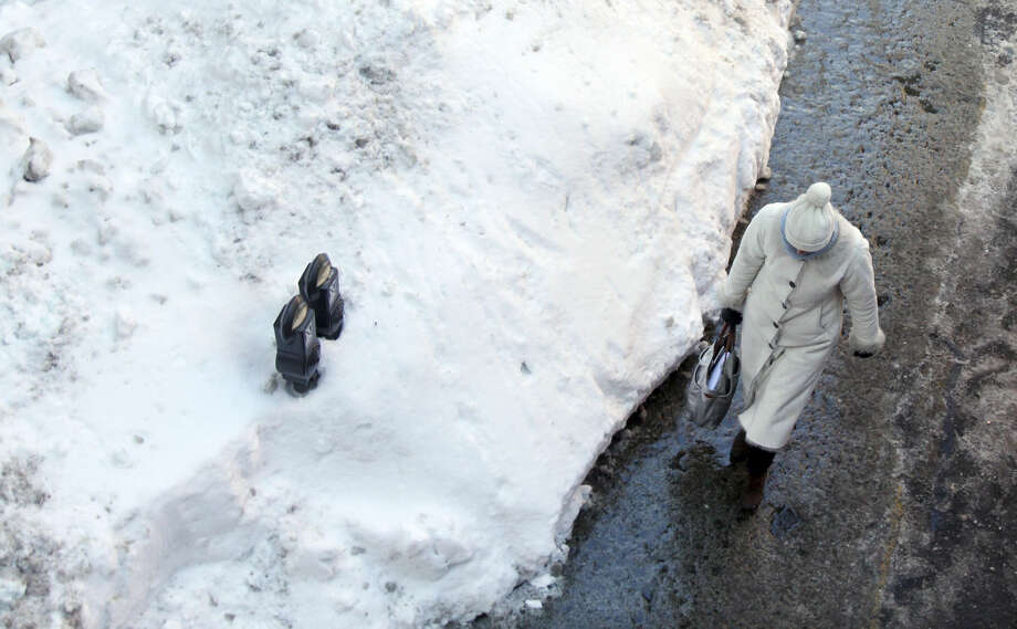 Parking meters sits mostly buried in a mound of snow Friday, Feb. 13, 2015, along a street in downtown Boston. Another winter storm that could bring an additional foot or more of snow to some areas is forecast for the region beginning Saturday evening. (AP Photo/Bill Sikes)