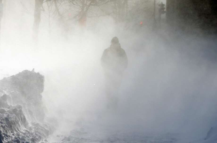 A pedestrian walks through drifting snow driven by strong wind in Boston, Sunday, Feb. 15, 2015. A storm brought a new round of wind-whipped snow to New England on Sunday, threatening white-out conditions in coastal areas and forcing people to contend with a fourth winter onslaught in less than a month. (AP Photo/Michael Dwyer)