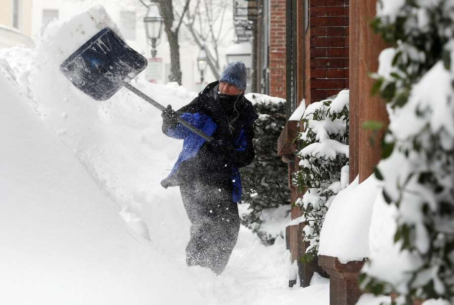 Judith Hanson shovels snow on Beacon Hill in Boston, Sunday, Feb. 15, 2015. A storm brought a new round of wind-whipped snow to New England on Sunday, accompanied by near-whiteout conditions and lightning strikes in coastal areas as people contended with a fourth winter onslaught in less than a month. (AP Photo/Michael Dwyer)