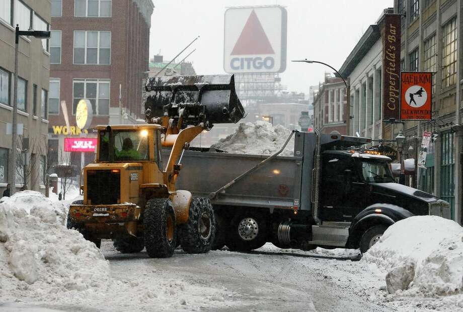 A crew from Connecticut clears snow from the street near Fenway Park in Boston, Saturday, Feb. 14, 2015. Crews from around the region have worked urgently to remove the massive amounts of snow that has clogged streets and triggered numerous roof collapses ahead of yet another winter storm due to arrive on Saturday. (AP Photo/Michael Dwyer)