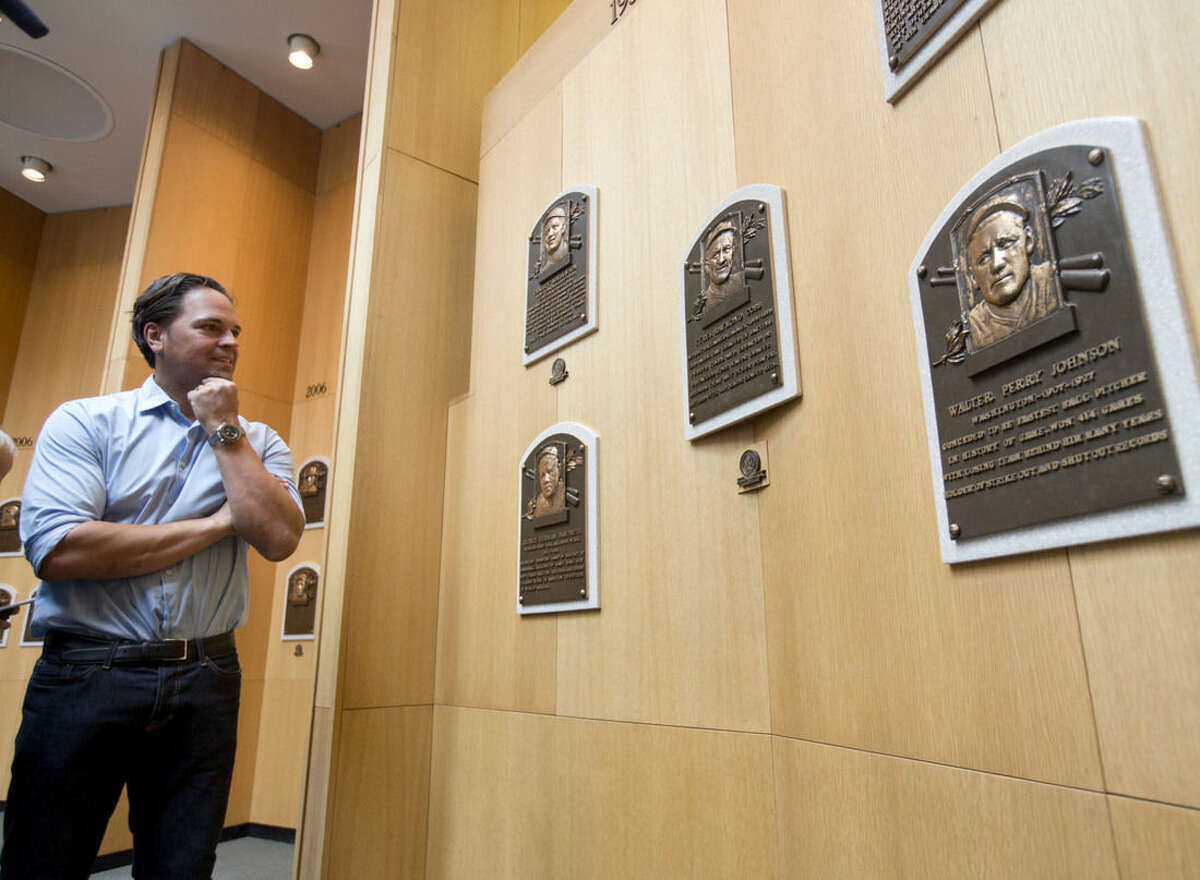 Baseball Hall of Fame electee Mike Piazza looks at plaques of original hall members during his orientation tour on Tuesday, March 8, 2016, in Cooperstown, N.Y. Piazza will be inducted in July. (AP Photo/Mike Groll)