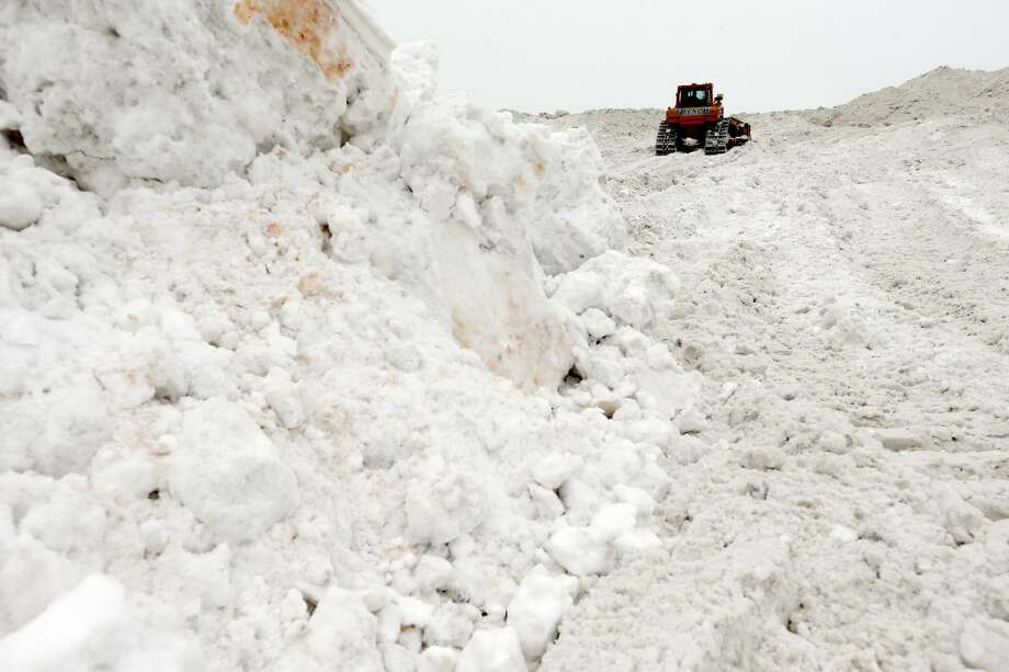 "A bulldozer works on a giant pile of snow at a ""snow farm"" in Boston, Saturday, Feb. 14, 2015. Crews from around the region have worked urgently to remove the massive amounts of snow that has clogged streets and triggered numerous roof collapses ahead of yet another winter storm due to arrive on Saturday. (AP Photo/Michael Dwyer)"