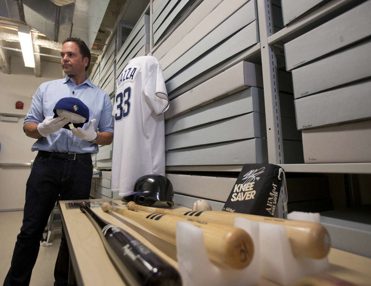 Baseball Hall of Fame electee Mike Piazza looks at some of his personal items in the archives area during his orientation tour at the hall on Tuesday, March 8, 2016, in Cooperstown, N.Y. Piazza will be inducted in July. (AP Photo/Mike Groll)