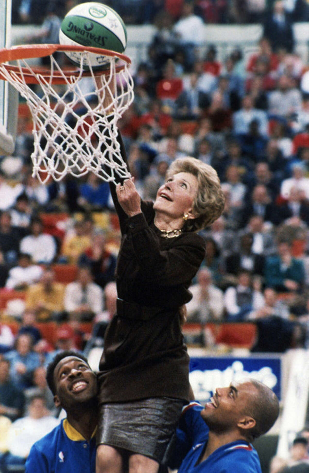 FILE - In this Feb. 4, 1988 file photo, then first lady Nancy Reagan, with the help of Indiana Pacer Wayman Tisdale, left, and Philadelphia 76er Charles Barkley, laughs as the ball drops through the net after her 'slam dunk' during halftime of an NBA basketball game in Indianapolis. Reagan was in town as part of the league-wide tribute to the