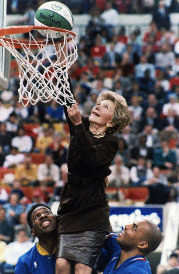 "FILE - In this Feb. 4, 1988 file photo, then first lady Nancy Reagan, with the help of Indiana Pacer Wayman Tisdale, left, and Philadelphia 76er Charles Barkley, laughs as the ball drops through the net after her 'slam dunk' during halftime of an NBA basketball game in Indianapolis. Reagan was in town as part of the league-wide tribute to the ""Just Say No"" campaign. Reagan, who died Sunday, March 16, 2016, is perhaps best known for her ""Just Say No"" to drugs and alcohol campaign. Three decades after the campaign's heyday, prevention experts credit it with spawning a new generation of research into the best ways of reducing drug abuse. But they also say that many of the fear-based tactics it embraced didn't work. (AP Photo/Michael Conroy, File)"