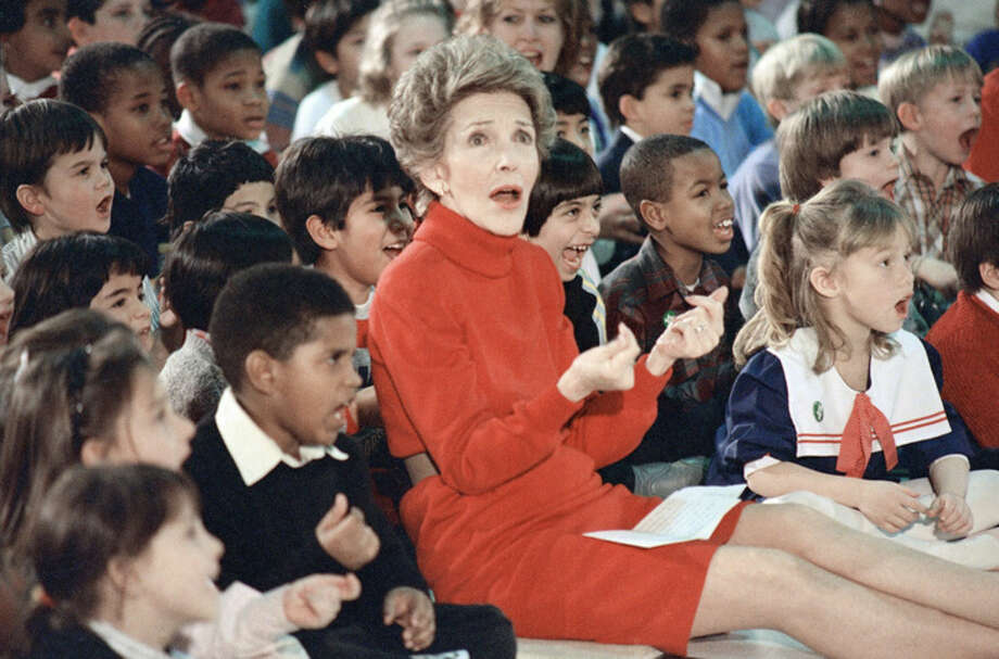 """FILE - In this Feb. 26, 1987 file photo, then first lady Nancy Reagan watches an anti-drug musical titled """"Just Say No,"""" performed by teenage students from the Chantilly, Va., High School Drama Department at the Cameron Elementary School in Alexandria, Va. Reagan, who died Sunday, March 6, 2016, is perhaps best known for her """"Just Say No"""" to drugs and alcohol campaign. Three decades after the campaign's heyday, prevention experts credit it with spawning a new generation of research into the best ways of reducing drug abuse. But they also say that many of the fear-based tactics it embraced didn't work. (AP Photo/Scott Stewart, File)"""