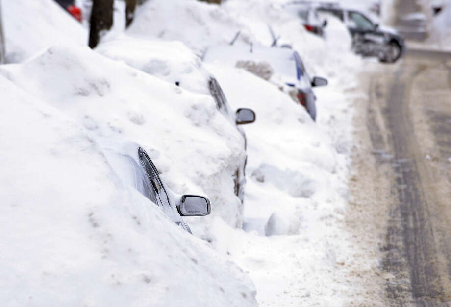 A line of cars sit buried in snow banks in Somerville, Mass., Tuesday, Feb. 10, 2015. The latest snowstorm left the Boston area with another two feet of snow and forced the MBTA to suspend all rail service for the day. (AP Photo/Josh Reynolds)