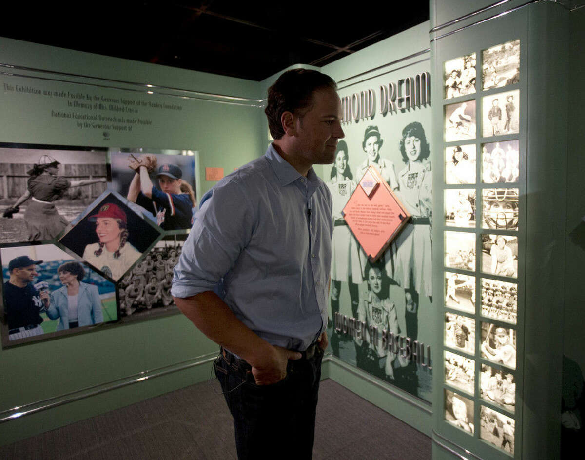 Baseball Hall of Fame electee Mike Piazza visits an exhibit on women in baseball during his orientation tour at the hall on Tuesday, March 8, 2016, in Cooperstown, N.Y. He will be inducted in July. (AP Photo/Mike Groll)