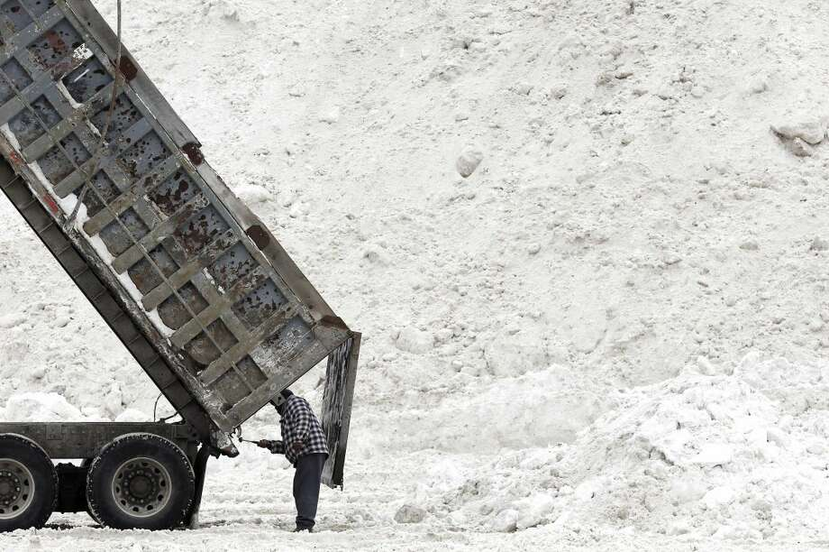 """Evon Daley, of Hartford, Conn., clears his truck after unloading snow at a """"snow farm"""" in Boston, Saturday, Feb. 14, 2015. Crews from around the region have worked urgently to remove the massive amounts of snow that has clogged streets and triggered numerous roof collapses ahead of yet another winter storm due to arrive on Saturday. (AP Photo/Michael Dwyer)"""