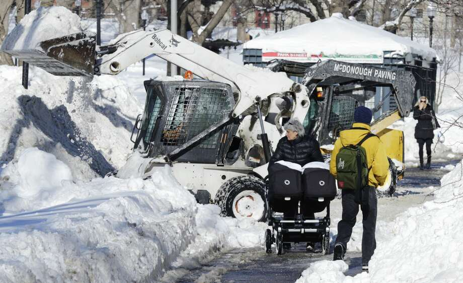 A woman pushes a baby carriage as front end loaders clear snow for Wednesday's Patriot's Super Bowl parade celebration along the Boston Common in Boston, Tuesday, Feb. 3, 2015. The Boston area has received about 40 inches of snow in the past week. (AP Photo/Charles Krupa)
