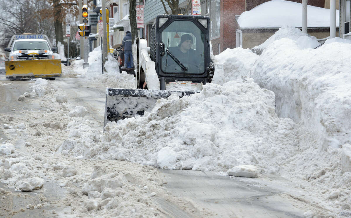 A worker uses a compact front-end loader to clear snow from a road to be removed by a dump truck near Davis Square in Somerville, Mass., Tuesday, Feb. 10, 2015. The third major winter storm in two weeks left the Boston area with another two feet of snow and forced the MBTA to suspend all rail service for the day. (AP Photo/Josh Reynolds)