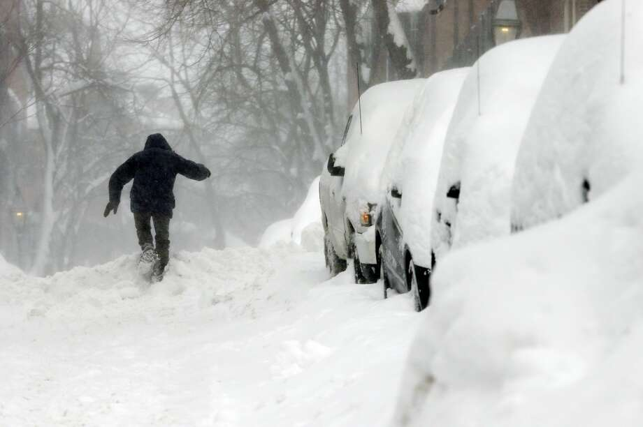 A man struggles through the snow on Beacon Hill in Boston, Sunday, Feb. 15, 2015. A storm brought a new round of wind-whipped snow to New England on Sunday, accompanied by near-whiteout conditions and lightning strikes in coastal areas as people contended with a fourth winter onslaught in less than a month. (AP Photo/Michael Dwyer)